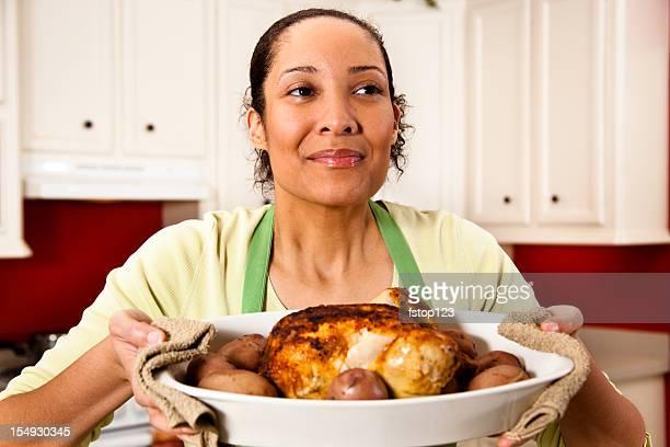 Woman in kitchen enjoying aroma of baked chicken dish.