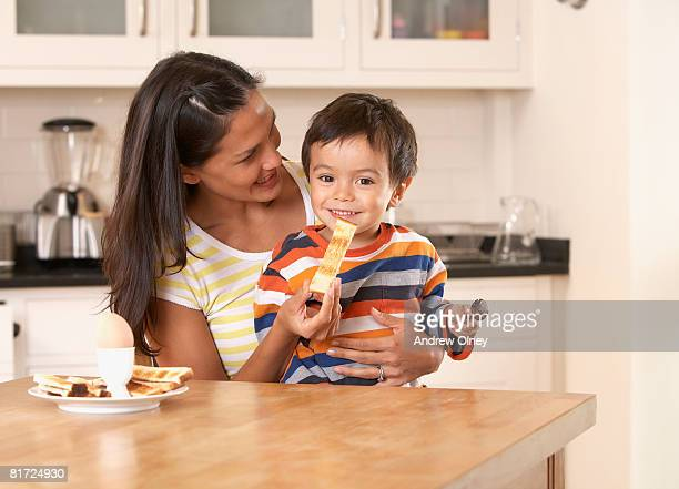 Woman in kitchen feeding young boy a piece of toast and smiling