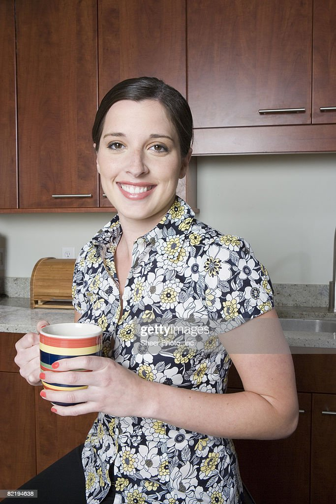 woman in kitchen holding cup : Stock Photo