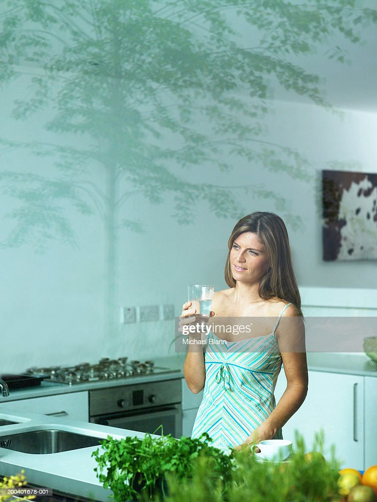 Woman In Kitchen Holding Glass Of Water Smiling View Through Window ...