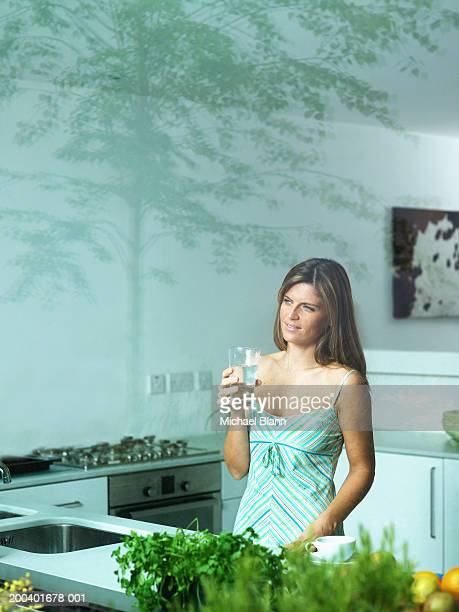 Woman in kitchen holding glass of water, smiling, view through window