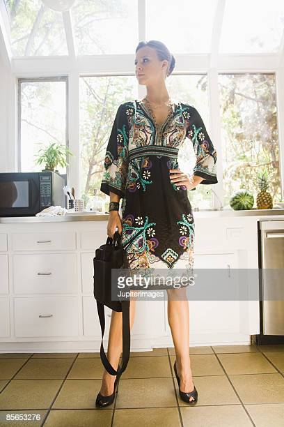 Woman in kitchen holding laptop case