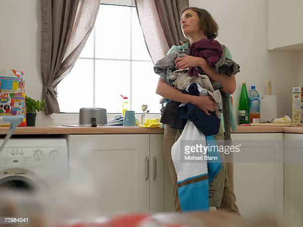 """Woman in kitchen holding laundry, looking careworn"""