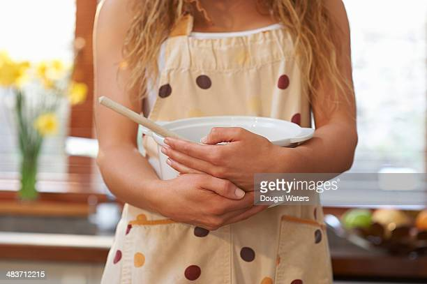 Woman in kitchen holding mixing bowl.