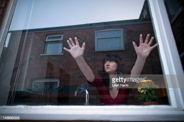 woman in kitchen leaning on window - trapped stock pictures, royalty-free photos & images