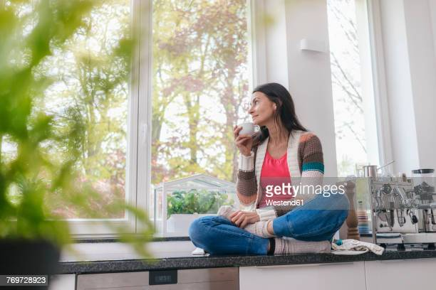 Woman in kitchen looking out of window