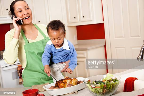 Woman in kitchen on phone and holding child making meal.