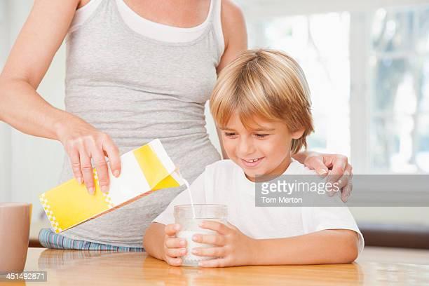 Mulher na cozinha Verter jovem rapaz copo de leite