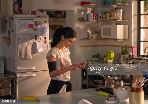 woman in kitchen preparing music for a run - morning - fotografias e filmes do acervo