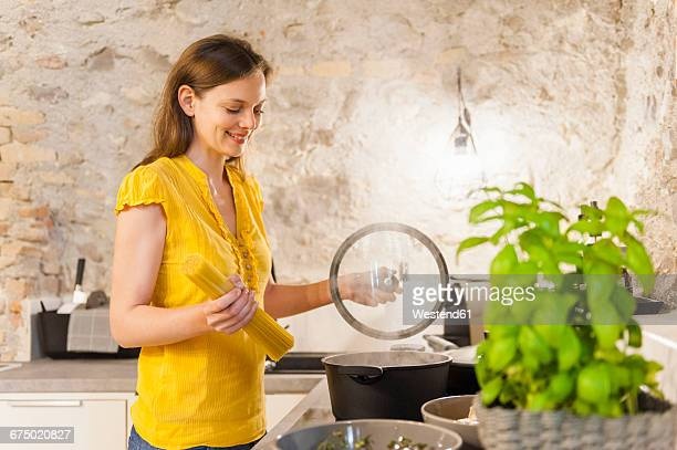 woman in kitchen preparing spaghetti - mid adult women stock pictures, royalty-free photos & images