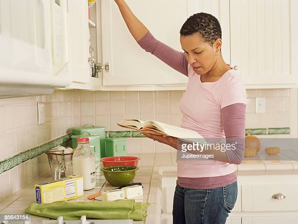 Woman in kitchen reading cookbook
