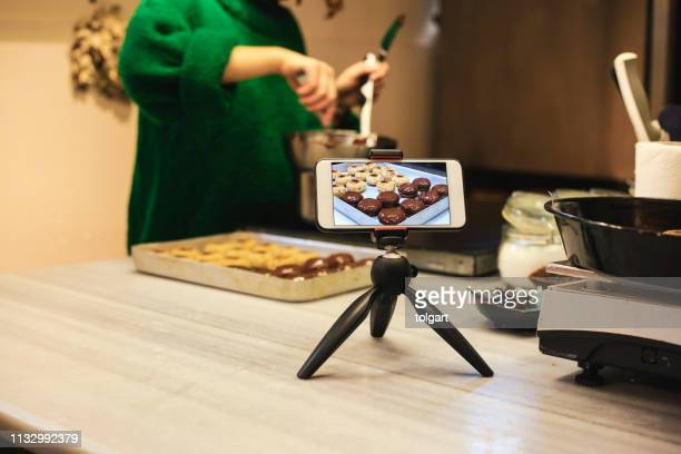 woman in kitchen recording video on mobile phone - camera icon stock pictures, royalty-free photos & images