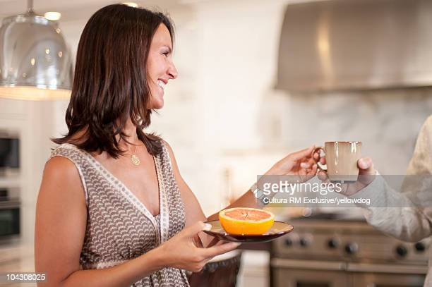 Woman in kitchen serving coffee and food