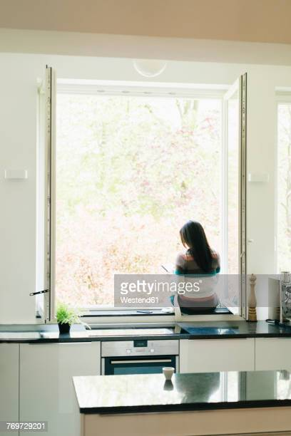 Woman in kitchen sitting on windowsill