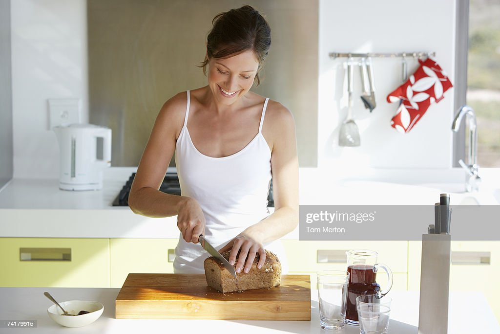 Woman in kitchen slicing bread : Stock Photo