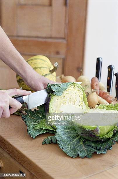 Woman in kitchen slicing savoy cabbage, close-up of hands