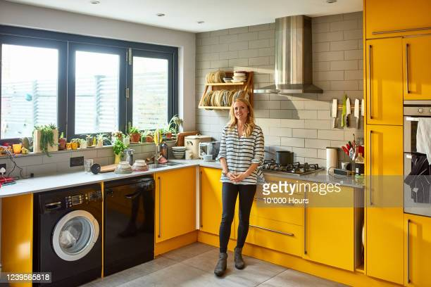 woman in kitchen smiling at camera - kitchen stock pictures, royalty-free photos & images