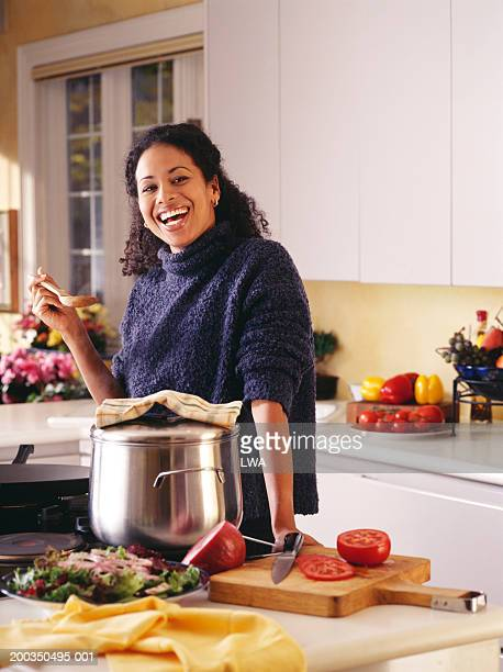 woman in kitchen smiling - burner stove top stock pictures, royalty-free photos & images