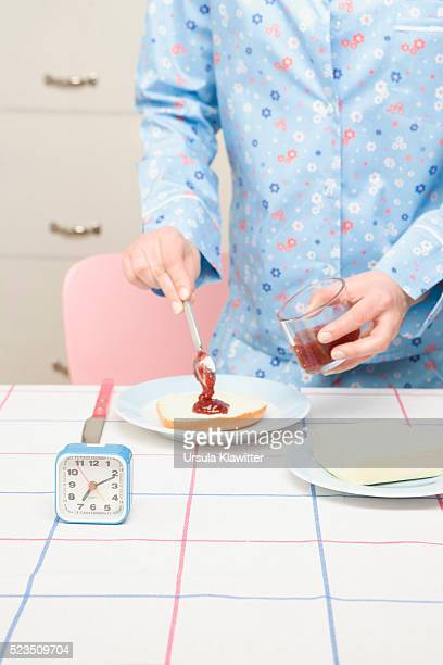Woman in Kitchen Spreading Jam on Bread Roll
