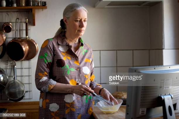 Woman in kitchen whisking bowl while looking at television screen