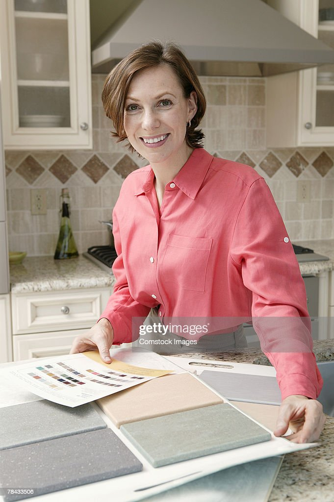 Woman in kitchen with tile samples : Foto de stock