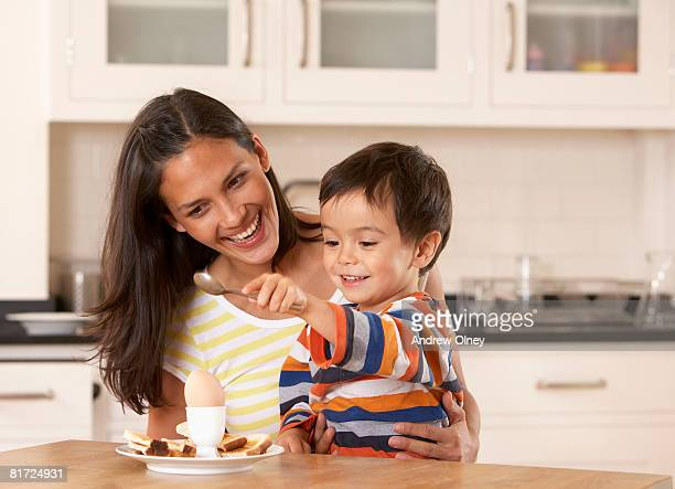 Woman in kitchen with young boy eating a boiled egg and toast
