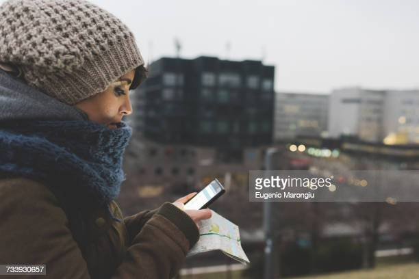 Woman in knit hat looking at smartphone in city at dusk