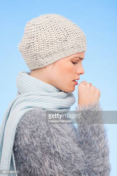 Woman in knitted hat and coughing