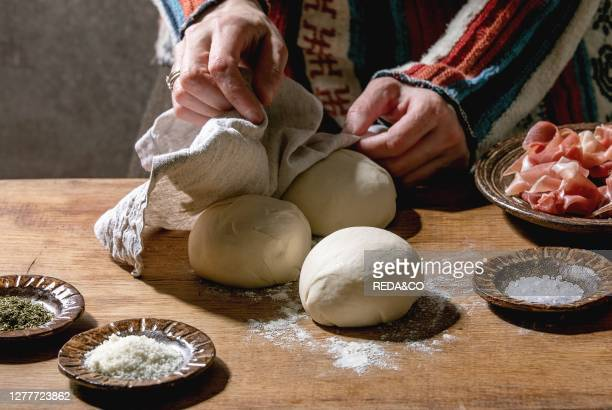 Woman in knitted sweater cooking italian pizza napolitana. Three balls of fresh homemade wheat dough, prosciutto and ingredients in ceramic plates...