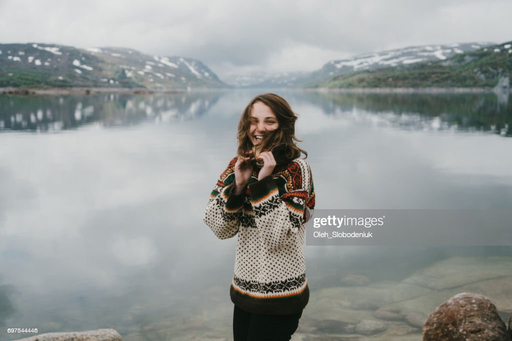Woman in knitted sweater laughing near the  fjord in Norway : Stock Photo