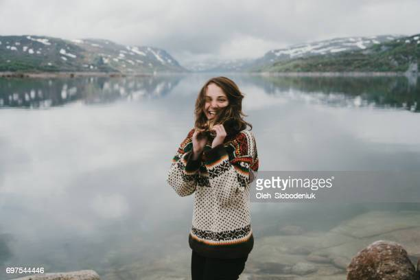 Woman in knitted sweater laughing near the  fjord in Norway