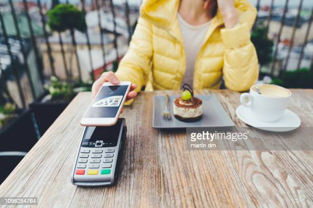 woman in krakow old town using digital wallet for mobile payment - malopolskie province stock pictures, royalty-free photos & images