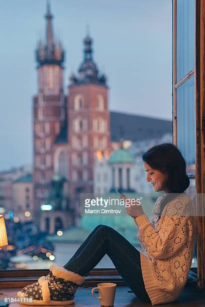 Woman in Krakow texting at the window