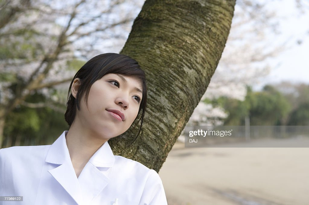 Woman in lab coat leaning on a tree trunk, front view, Japan : Photo