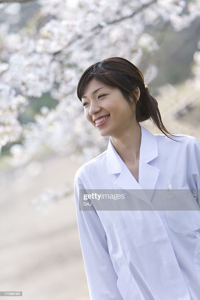 Woman in lab coat smiling and standing under the cherry tree, front view, Japan : Photo