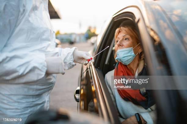 ドライブスルー医療検査場で60代後半の女性 - ドライブスルー検査 ストックフォトと画像