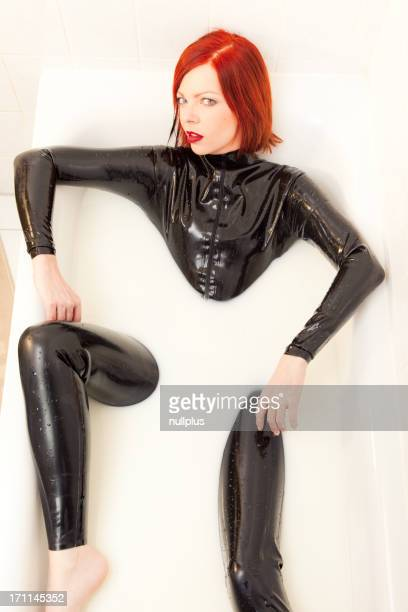 woman in latex catsuit taking a bath