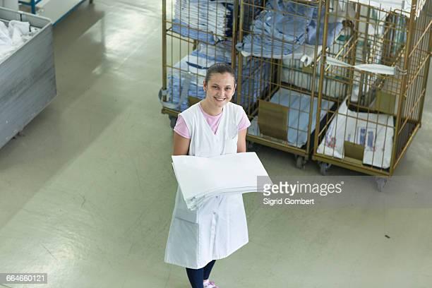 woman in launderette holding folded laundry - sigrid gombert stock-fotos und bilder
