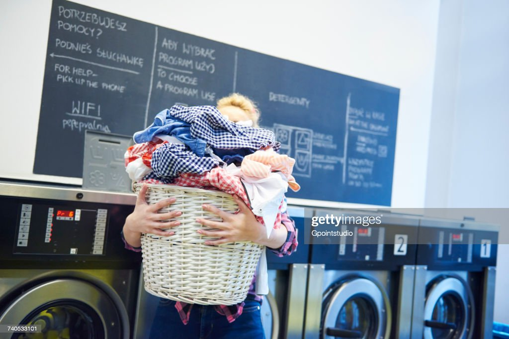 Woman in laundrette carrying full laundry basket : ストックフォト