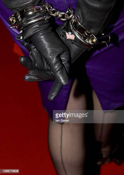 A woman in leather gloves and handcuffs walks around the hall during Erotica 2010 at Olympia Exhibition Centre on November 19 2010 in London England
