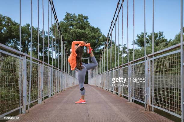woman in leggings stretching in yoga pose - orange shoe stock photos and pictures