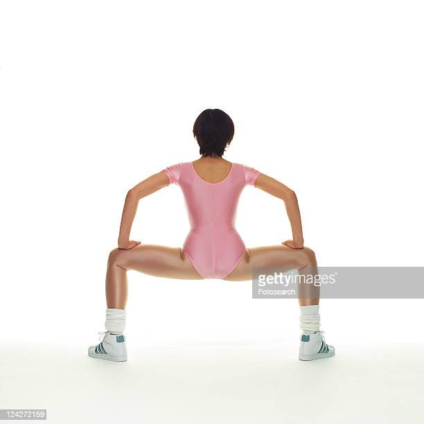 a woman in leotard exercising, rear view, copy space - frau gespreizte beine stock-fotos und bilder