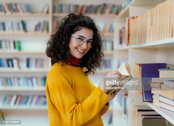 donna in biblioteca - authors foto e immagini stock