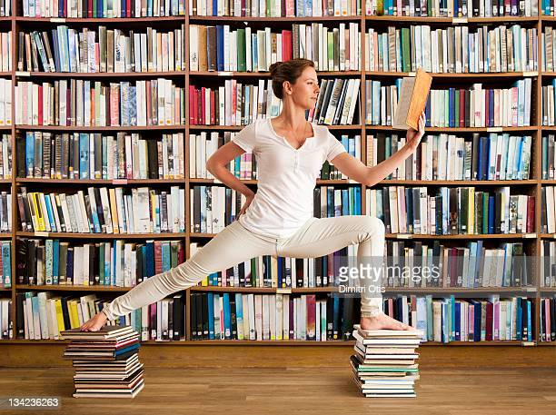 woman in library reads book and holds yoga pose - benen gespreid stockfoto's en -beelden