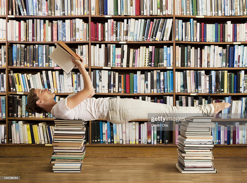 Woman in library reads book and holds yoga pose : Stock Photo