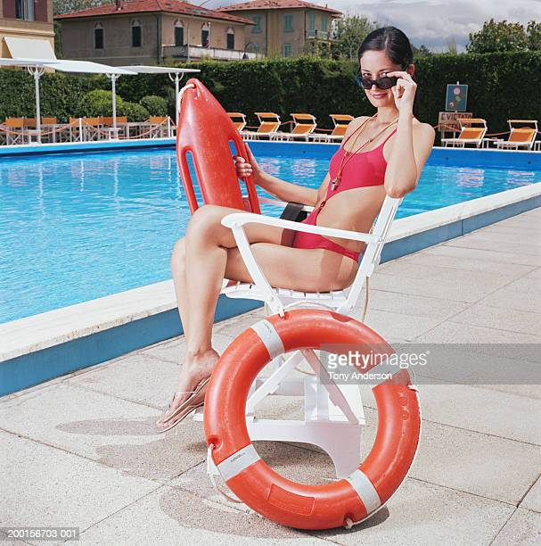 Woman in life guards seat by pool, portrait