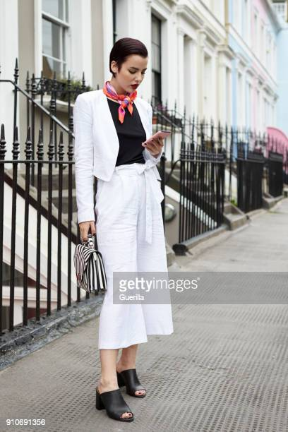 woman in linen suit looking at phone in street, full length - trousers stock pictures, royalty-free photos & images