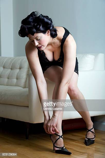woman in lingerie fastening high heels - bend over cleavage stock photos and pictures