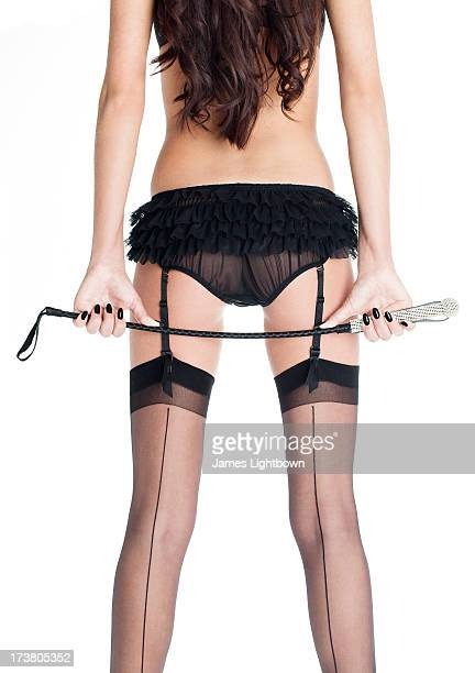 woman in lingerie holding riding crop - fesselung sadomasochismus stock-fotos und bilder