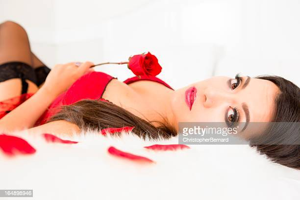 Woman in lingerie holding rose laying on bed